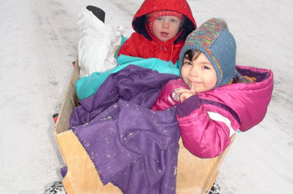 Die Tagespflegekinder fahren im Bollerwagen durch den braunschweiger Schnee.