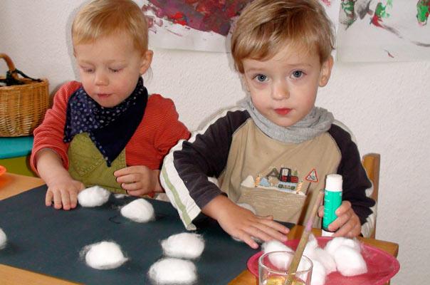 Tageskinder in der Kindertagespflege basteln Schneeflocken aus Watte und Kartoffeldruck.