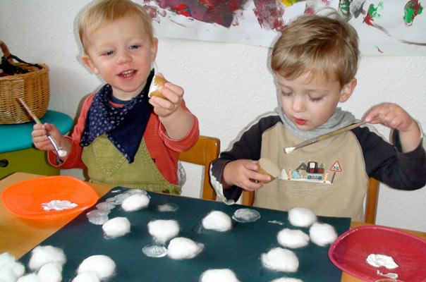 Tageskinder in der Kindertagespflege in Braunschweig basteln Schneeflocken aus Watte und Kartoffeldruck.